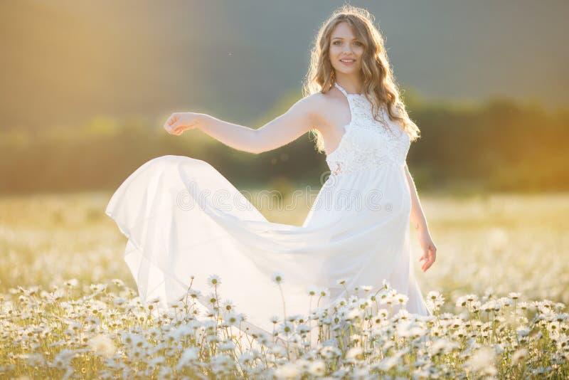 A menina grávida feliz bonita no campo da margarida floresce, tempo do por do sol foto de stock royalty free