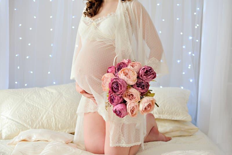 A menina grávida na roupa interior bege na cama mostra seu estômago e guarda flores em sua mão imagens de stock royalty free