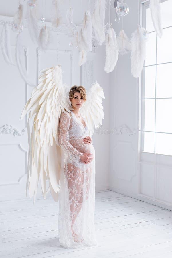 A menina grávida nova bonita com anjo grande voa fotos de stock royalty free