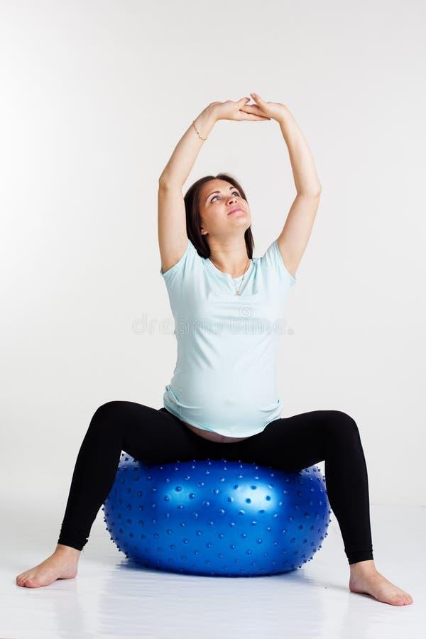 Menina grávida que faz exercícios de respiração no estúdio imagem de stock