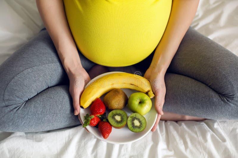 Menina grávida que guarda uma bacia de fruto imagens de stock