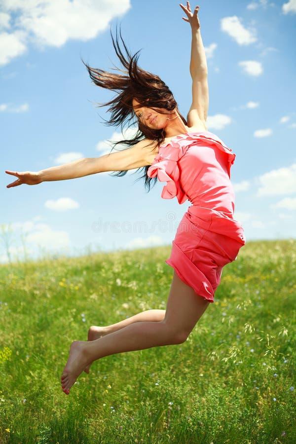 Menina graciosa de salto e de voo no fundo do céu azul foto de stock