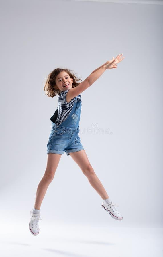 Menina graciosa que estica seus braços como salta foto de stock royalty free