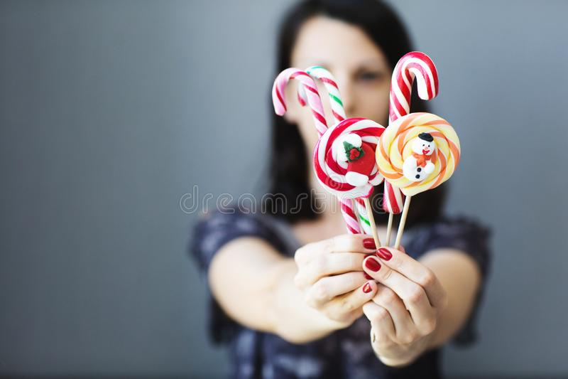 A menina guarda doces coloridos do Natal em suas mãos Doces no primeiro plano Conceito do Natal fotos de stock royalty free