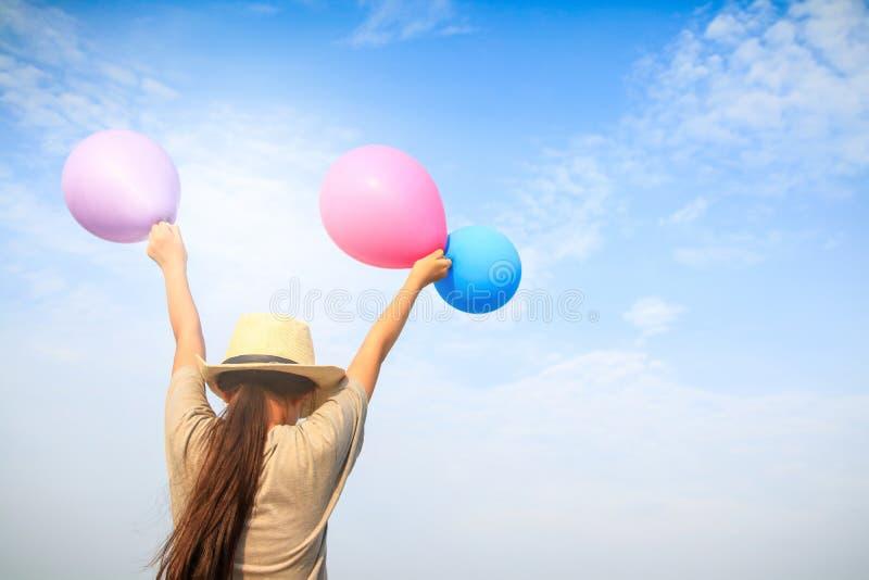 A menina guarda muitos balões coloridos imagem de stock royalty free