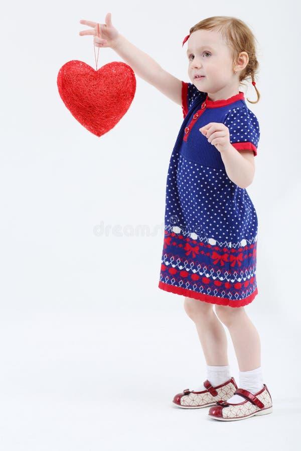 A menina guarda o coração vermelho em sua mão estendido imagem de stock
