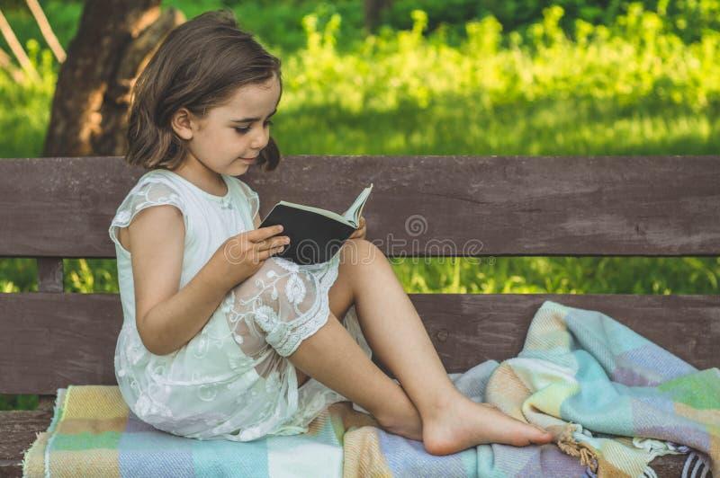 A menina guarda o livro em suas mãos Lendo o livro dentro no ar livre A menina no assento em um banco imagens de stock