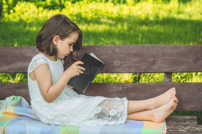 A menina guarda o livro em suas mãos Lendo o livro dentro no ar livre A menina no assento em um banco foto de stock royalty free