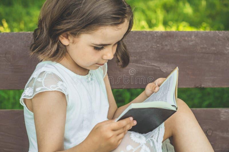 A menina guarda o livro em suas mãos Lendo o livro dentro no ar livre A menina no assento em um banco fotografia de stock royalty free