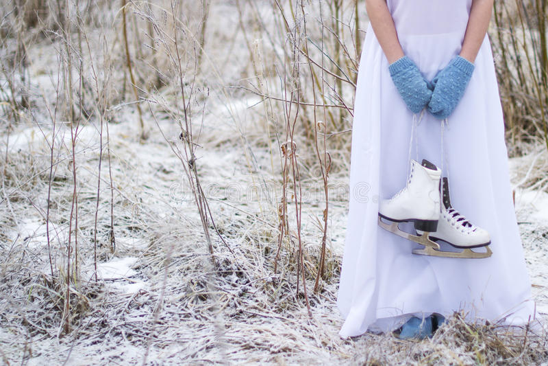 A menina guarda os patins para a patinagem artística fotografia de stock