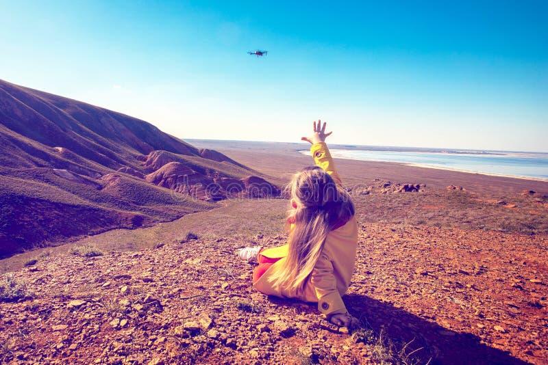 A menina guarda para fora suas mãos ao quadcopter Fotografia do zang?o fotos de stock