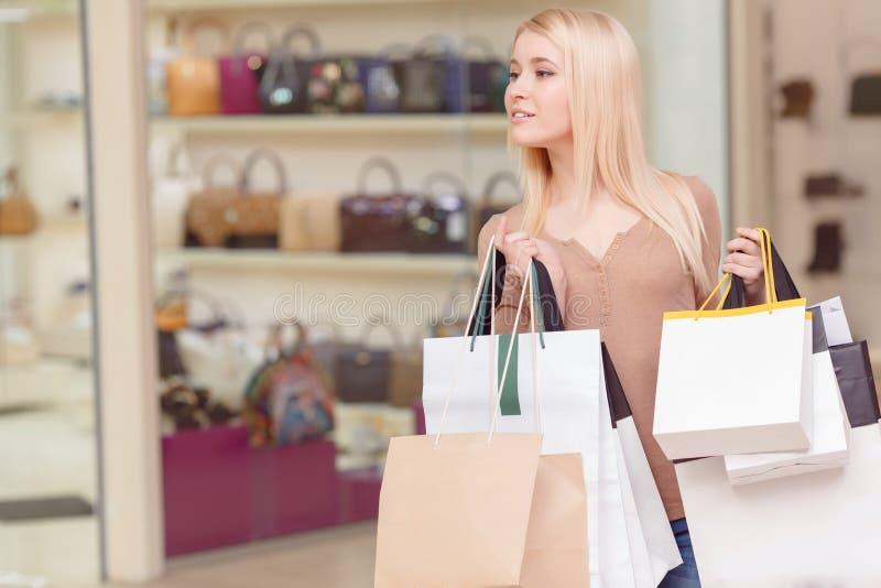 A menina guarda sacos de compras em suas mãos imagem de stock