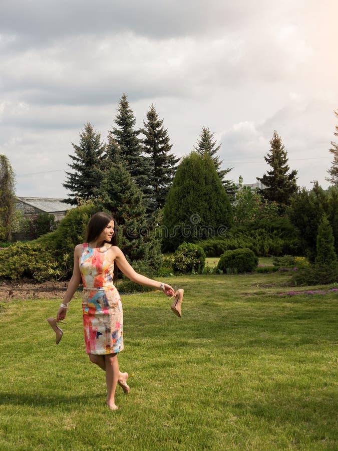 A menina guarda sapatas em suas mãos e caminhadas descalças na grama Resto para os pés imagem de stock