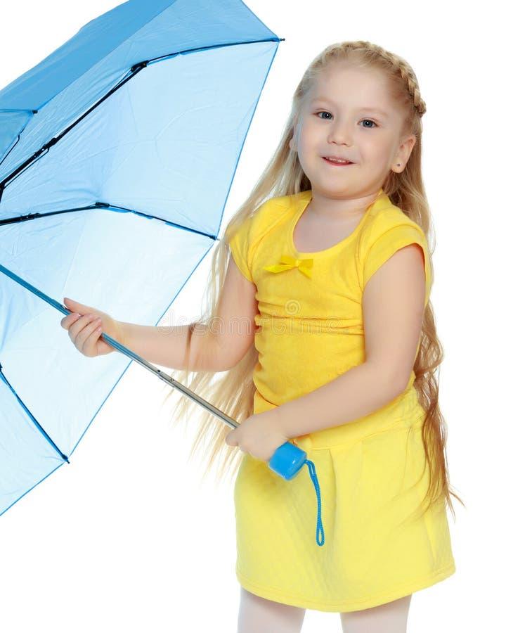A menina guarda um guarda-chuva azul em suas mãos imagem de stock royalty free