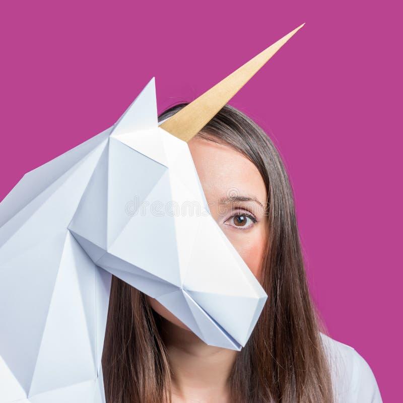 A menina guarda um modelo branco do papercraft 3d do unicórnio Art Concept mínimo fotos de stock royalty free