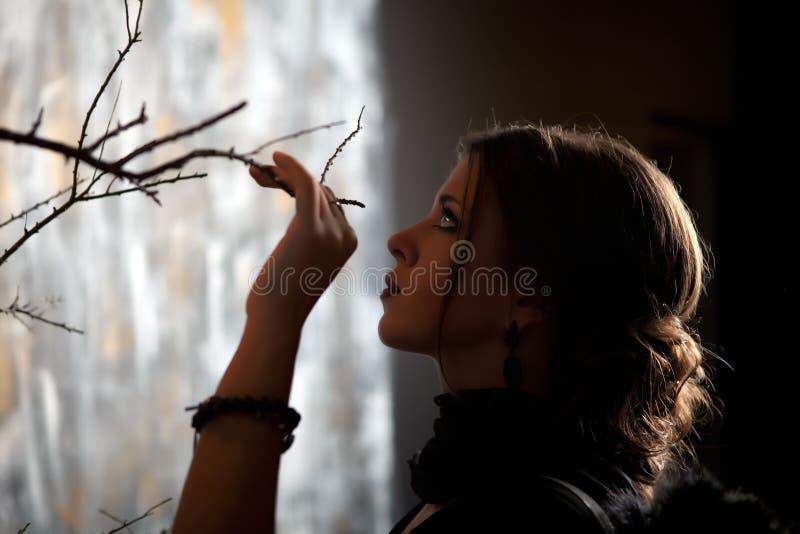 A menina guarda um ramo de árvore da mão imagem de stock