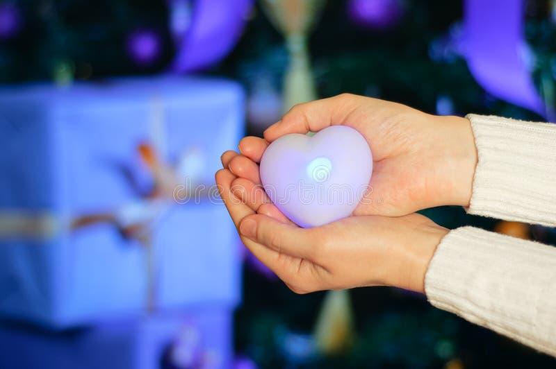 A menina guarda uma decoração luminosa do coração em suas mãos No fundo de presentes do Natal imagem de stock