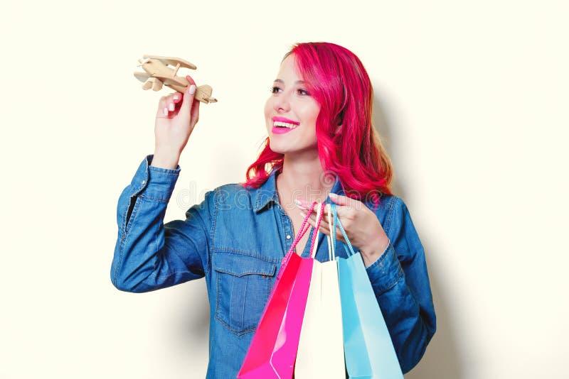 Menina guardando sacos de compras e o avião coloridos imagens de stock
