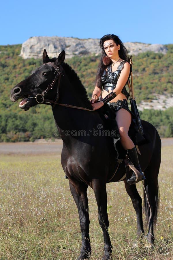 Menina-guerreiro - Amazonas armadas com a curva e as setas fotografia de stock