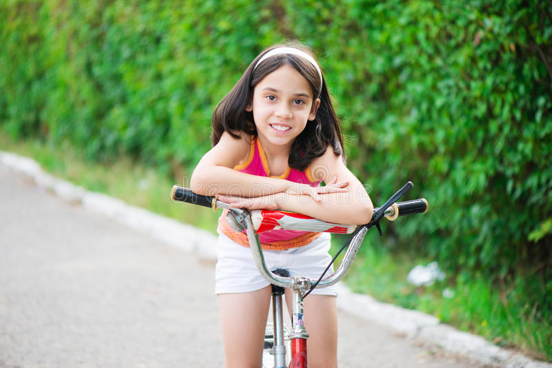 Menina hicpanic bonito na bicicleta foto de stock royalty free