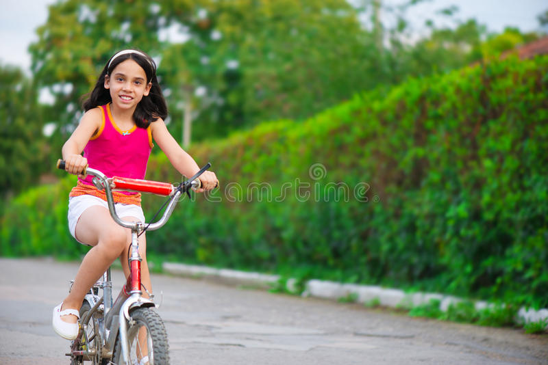 Menina hicpanic bonito na bicicleta imagens de stock