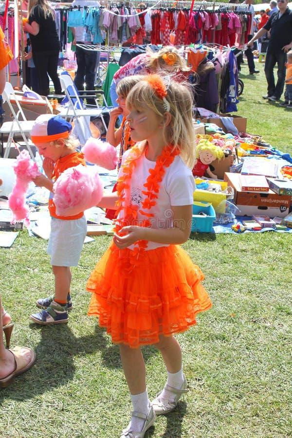 A menina holandesa no vestido alaranjado da princesa aprecia o algodão doce, Holanda fotos de stock