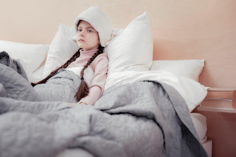 Menina impassível doente que encontra-se na cama imagem de stock royalty free