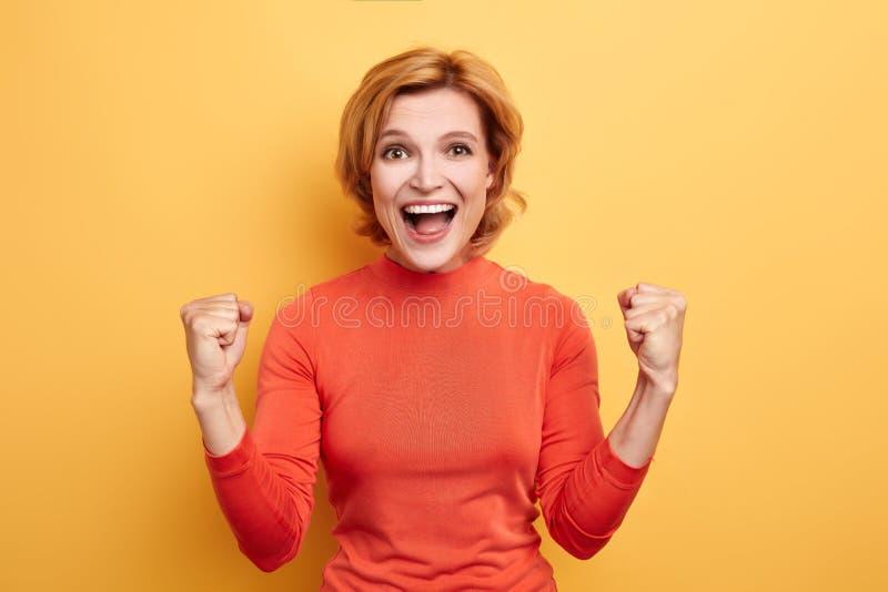 Menina impressionante no júbilo à moda vermelho da camiseta do rolo-pescoço na vitória de sua equipe fotos de stock