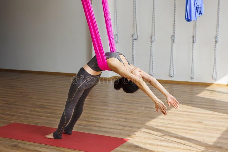 A menina inclina-se para trás com a rede que faz exercícios aéreos da ioga imagem de stock
