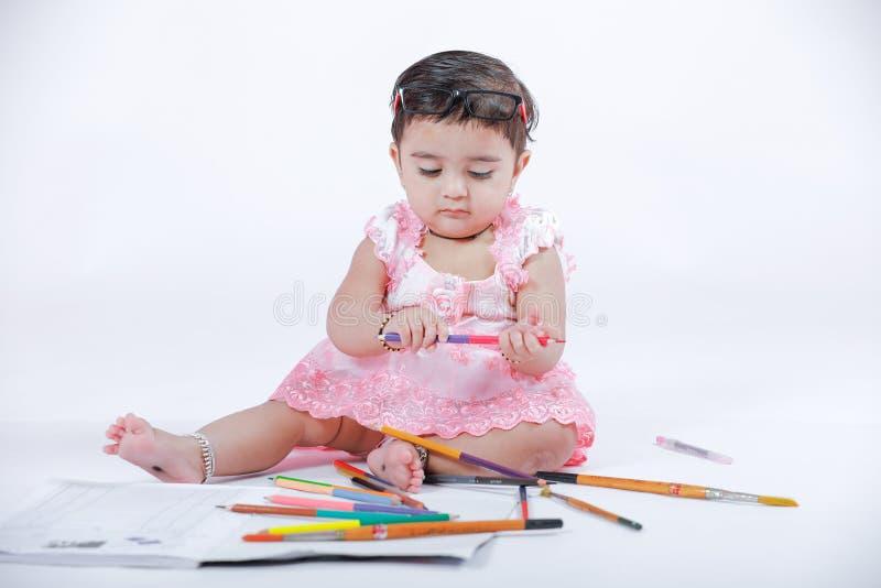 Menina indiana/asiática pequena bonito que aprecia a pintura com papel, pencle da cor e escova da arte imagem de stock royalty free