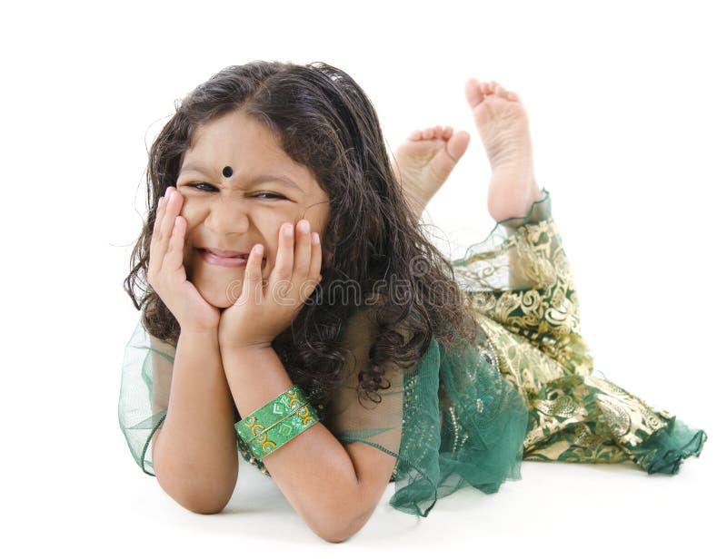 Menina indiana pequena que encontra-se no assoalho foto de stock