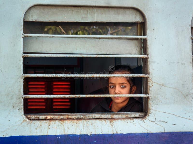 Menina indiana que senta-se no trem, e olhando através da janela do trem em Sambhar Rajasthan India imagem de stock