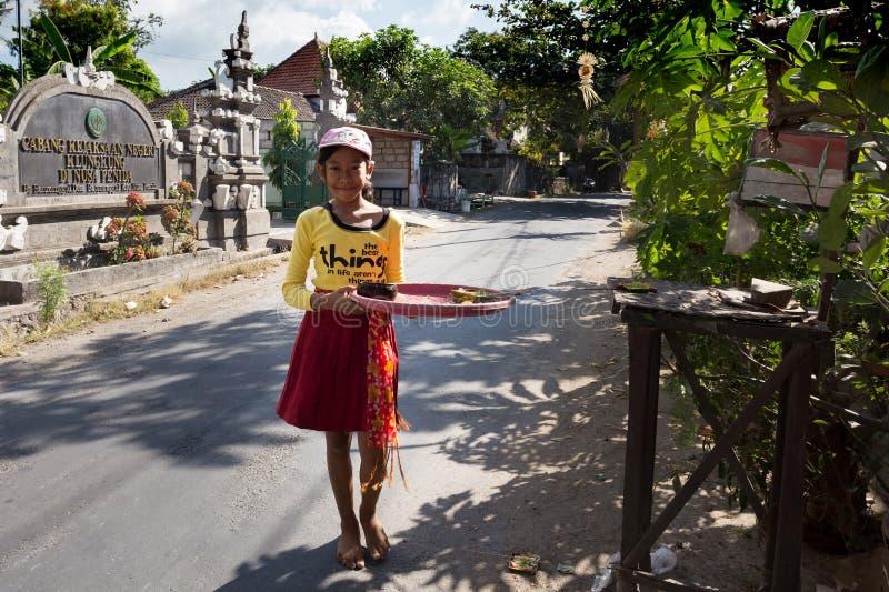 A menina indonésia traz ofertas ao templo home fotos de stock royalty free