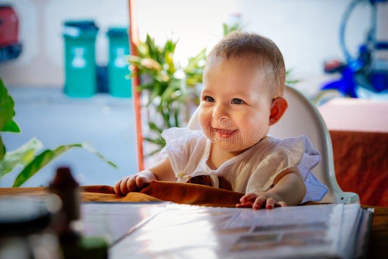 A menina infantil de sorriso feliz está sentando-se em uma cadeira alta do bebê no restaurante fotografia de stock