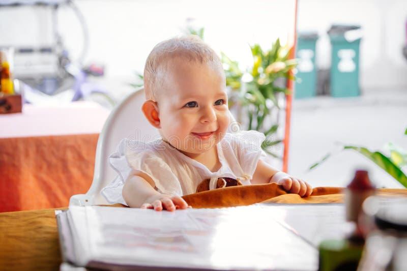 A menina infantil de sorriso feliz está sentando-se em uma cadeira alta do bebê em um café da rua Crianças que leem o menu no res fotografia de stock