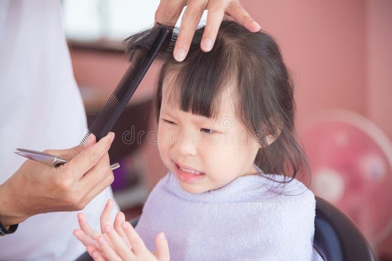 Menina infeliz com primeiro corte de cabelo pelo cabeleireiro imagens de stock