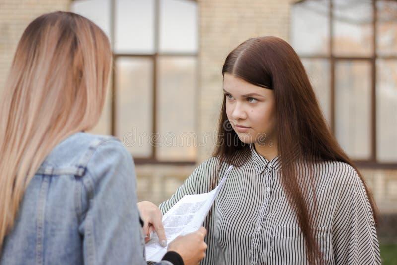 A menina infeliz está estando perto da universidade e do olhar no adulto com papel fotografia de stock