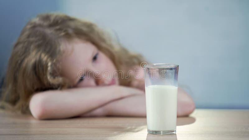 A menina infeliz não quer beber o leite, olhando o vidro, nutrição saudável fotos de stock