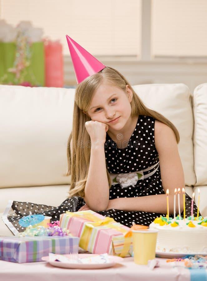 A menina infeliz no chapéu do partido senta-se com presentes fotografia de stock