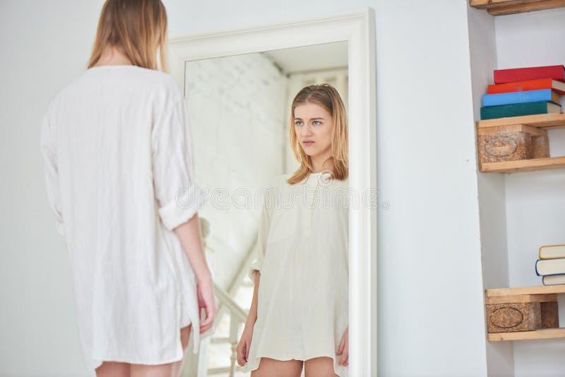 Menina infeliz que está perto do espelho imagens de stock royalty free