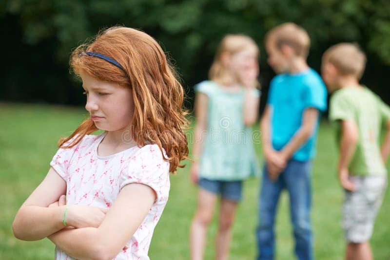 Menina infeliz que está sendo bisbilhotada aproximadamente por outras crianças imagem de stock royalty free