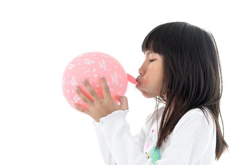 A menina infla um balão cor-de-rosa com mensagem o do feliz aniversario imagens de stock royalty free