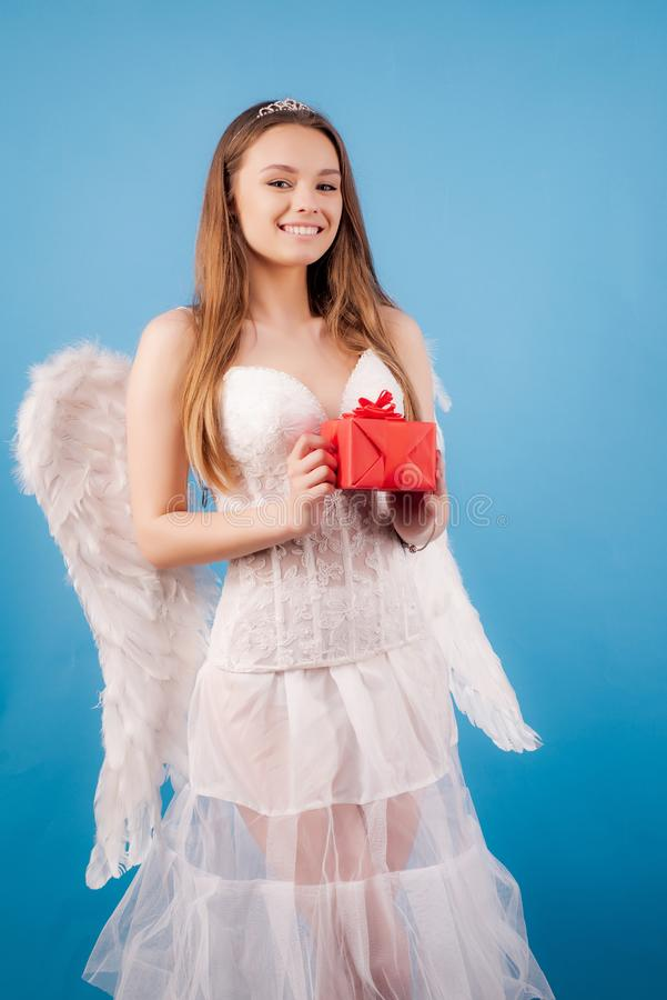 Menina inocente com as asas do anjo que estão com curva e seta contra o fundo branco isolado Anjo adolescente Dia do Valentim fotografia de stock royalty free