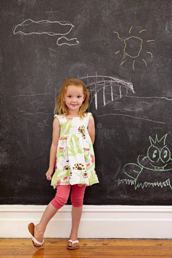 Menina inocente que está com desenhos de giz em casa imagem de stock