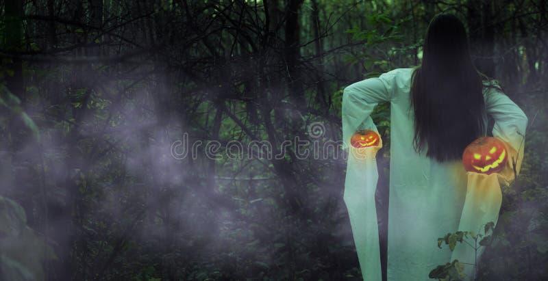 Menina inoperante com Jack-o-lanterna em uma floresta enevoada na noite imagem de stock