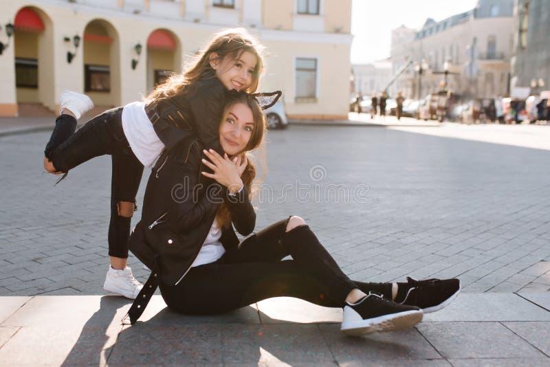 Menina inspirada em calças de brim na moda com furos que abraça a mãe, estando em um pé Jovem mulher surpreendida com pés longos imagens de stock royalty free