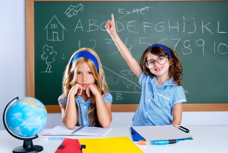 Menina inteligente do estudante do lerdo na sala de aula que levanta a mão fotografia de stock