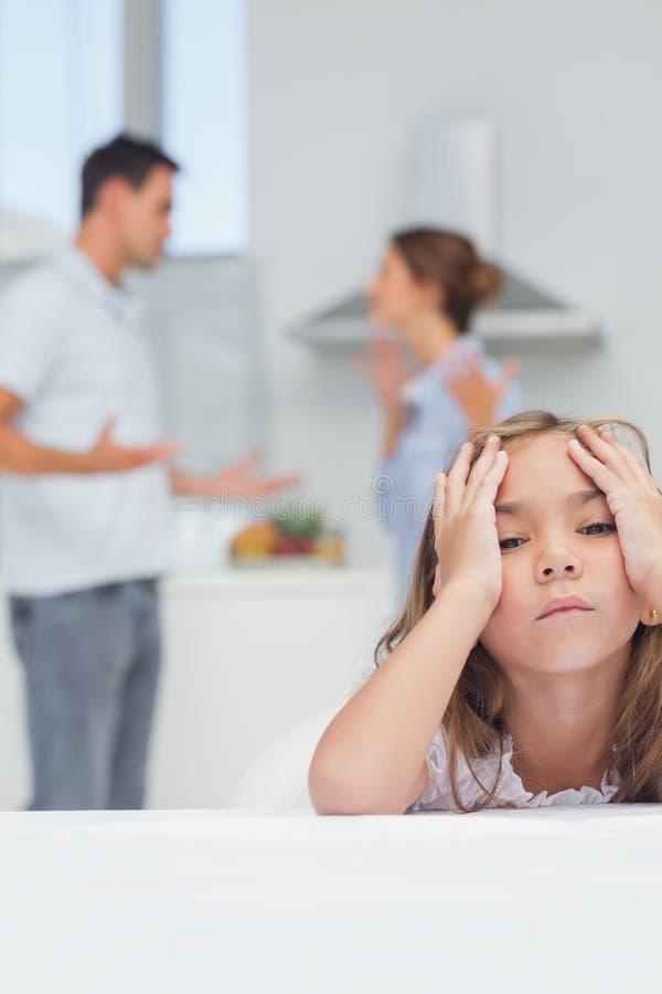 Menina irritada ao escutar os pais que discutem foto de stock royalty free