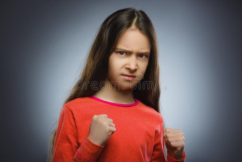 Menina irritada com gritar da mão acima isolado no fundo cinzento foto de stock