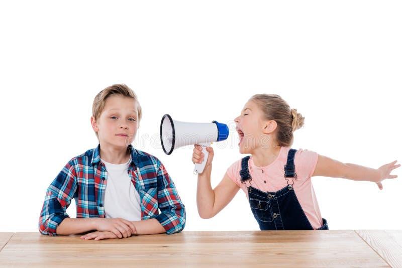 Menina irritada com megafone que grita em seu irmão imagem de stock royalty free